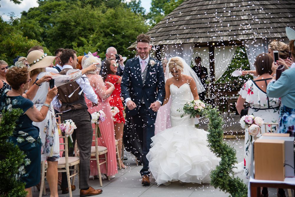 Bride and Groom on wedding day with family throwing confetti